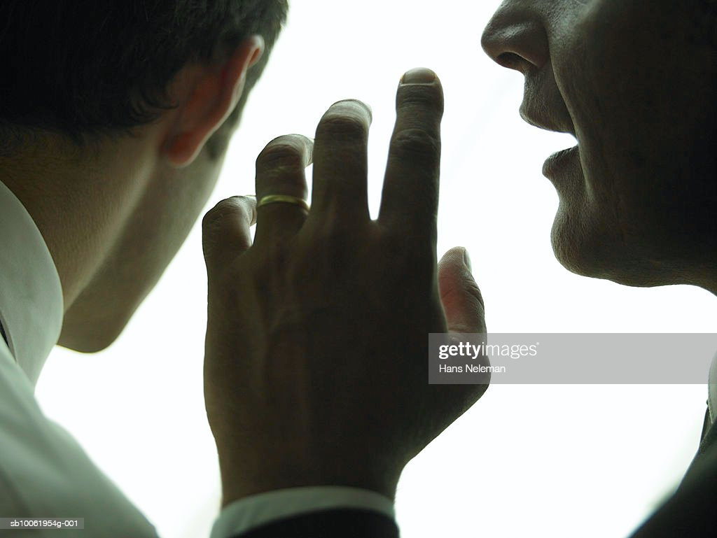 Businessman whispering another businessman, close-up : Stock Photo