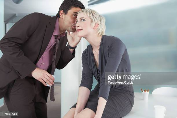 businessman whispering in co-worker's ear - side by side stock photos and pictures