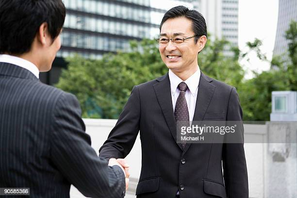 businessman who shakes hands with client - 45 49歳 ストックフォトと画像