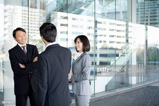 Businessman who speaks happily with companion.