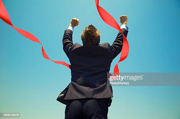Businessman Winning Success Outdoors at Red Finish Line Blue Sky