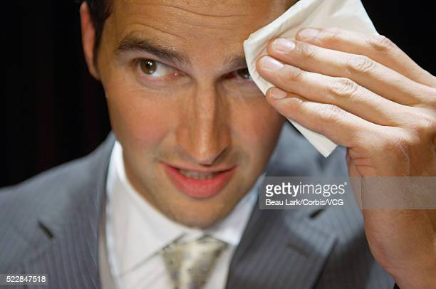 Businessman wiping forhead with handkerchief