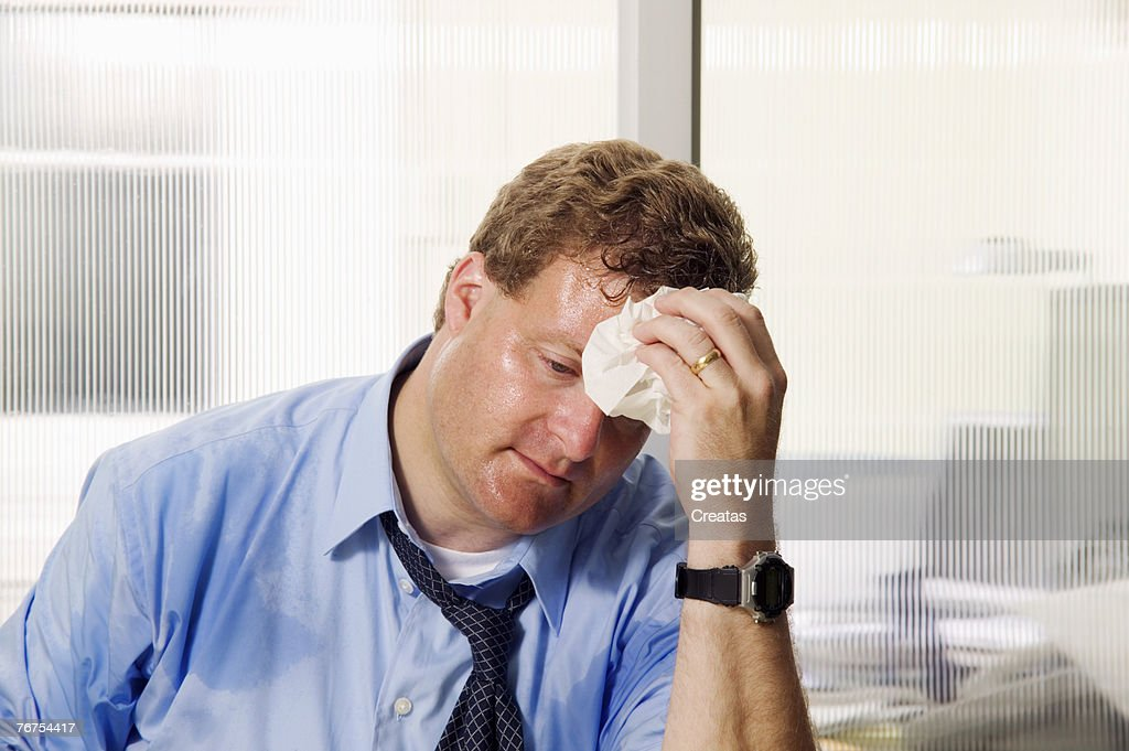 Businessman wiping his brow : Stock Photo
