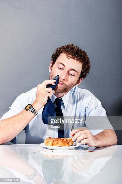 Businessman wiping his mouth with his tie