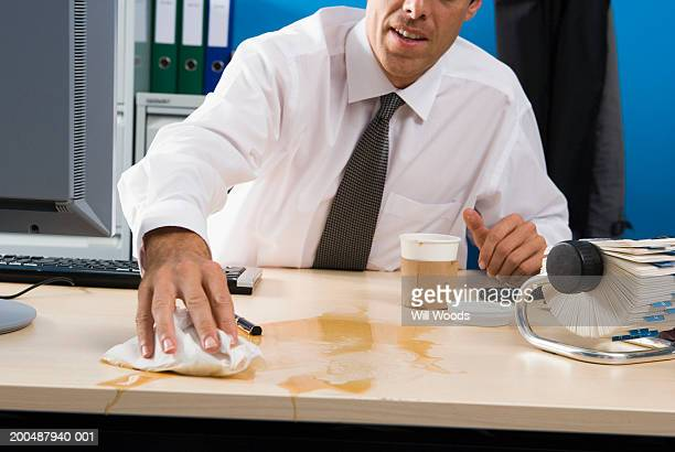 Businessman wiping spilt coffee on desk