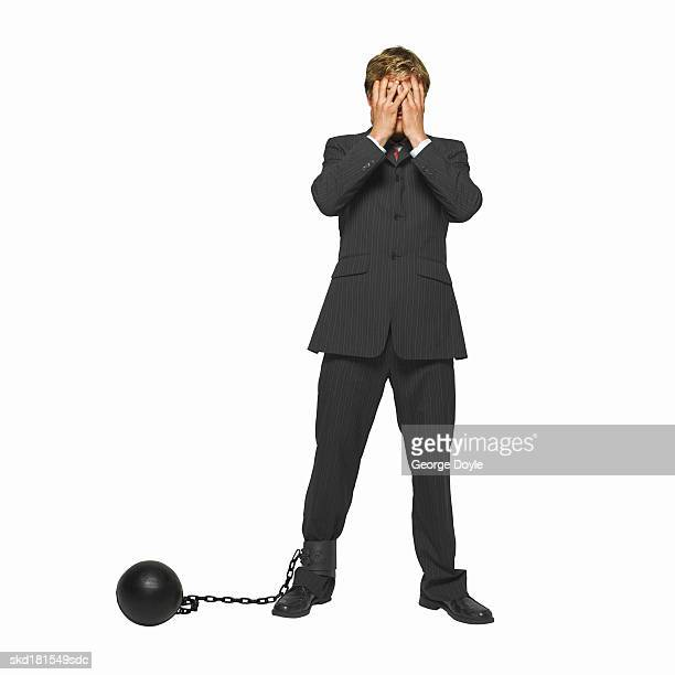 businessman with a ball and chain attached to his leg, covering his face with his hands