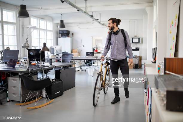 businessman with a bicycle in office - arrival stock pictures, royalty-free photos & images