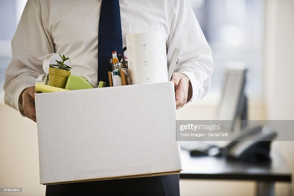 A businessman with a box full of desk stuff : Stock Photo