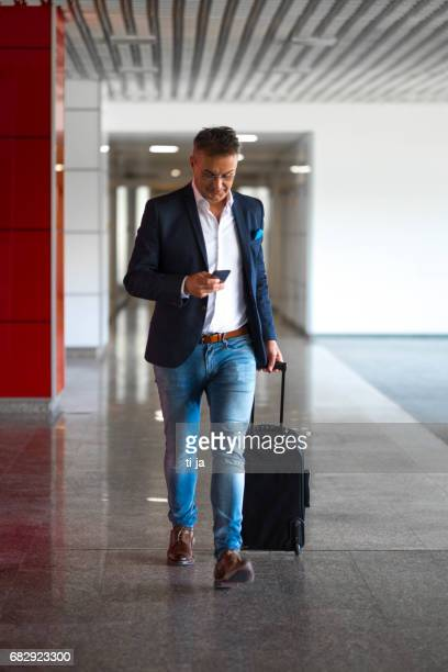 Businessman with a cell phone and a suitcase