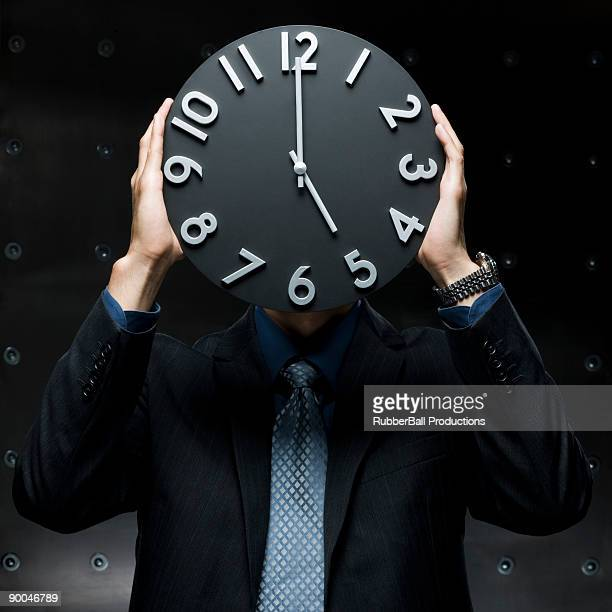 businessman with a clock in front of his face