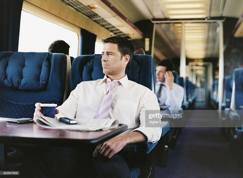 Businessman With a Cup of Coffee on a Passenger Train : Stock Photo
