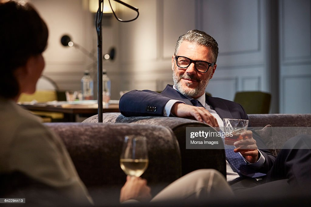 Businessman with a drink sitting in hotel : Stock Photo