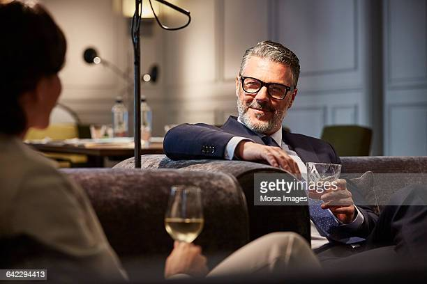 businessman with a drink sitting in hotel - whiskey stock pictures, royalty-free photos & images