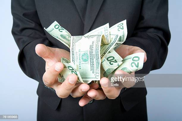 A businessman with a handful of US bank notes