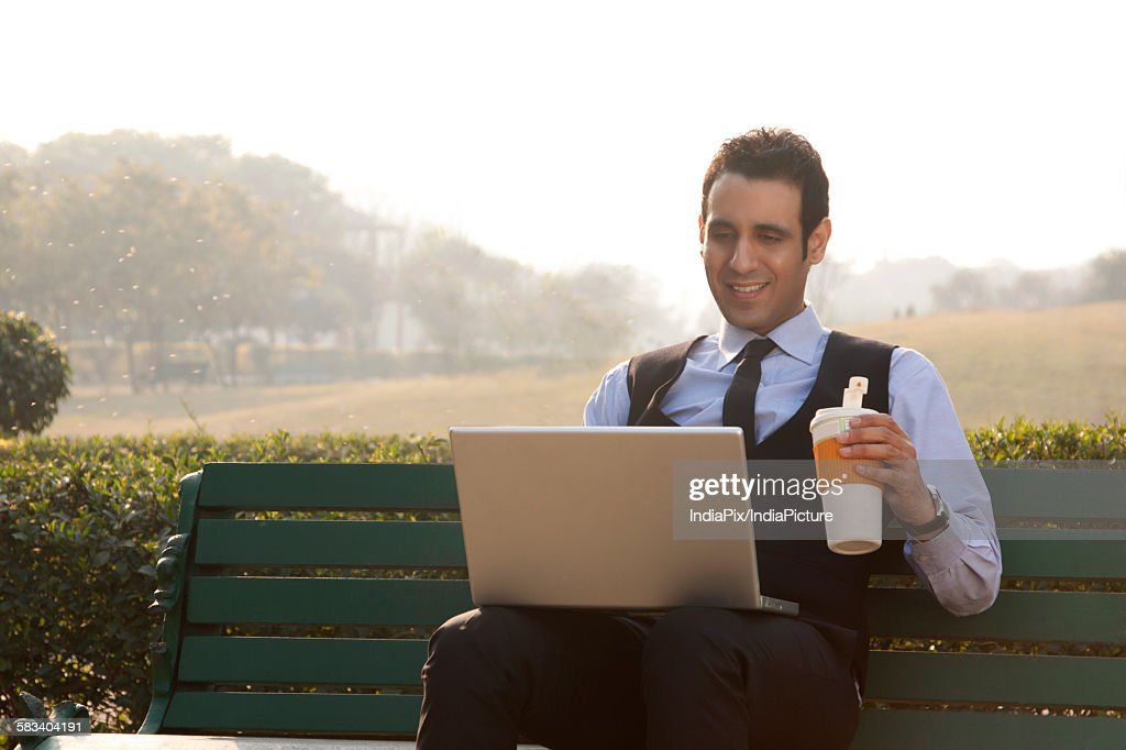 Businessman with a laptop and drink , INDIA , DELHI : Stock Photo