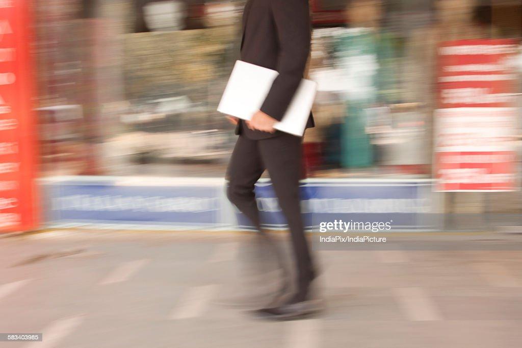 Businessman with a laptop walking , INDIA , DELHI : Stock Photo