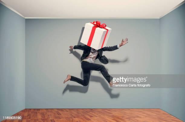 businessman with a large gift package - fugir da realidade imagens e fotografias de stock