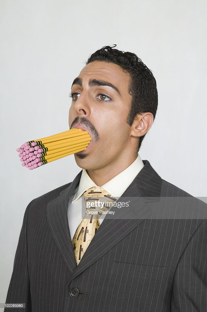 Businessman with a mouth full of pencils : Stock Photo