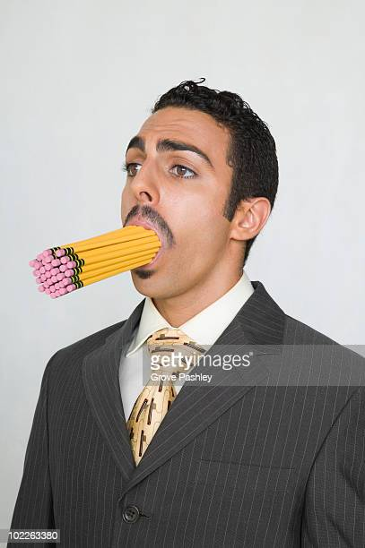 Businessman with a mouth full of pencils