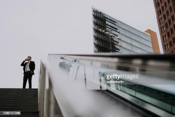 エスカレーターの近くにスマート フォンを持ったビジネスマン - geschäftsmann ストックフォトと画像