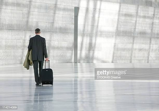businessman with a suitcase, rear view - wheeled luggage stock photos and pictures