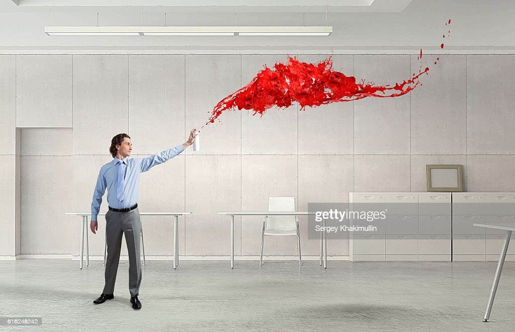 Businessman with aerosol can . Mixed media : Stock Photo