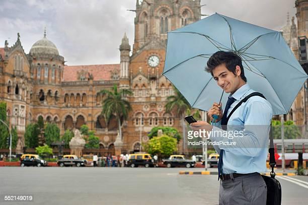 Businessman with an umbrella reading an sms