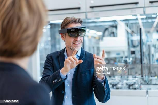 businessman with ar glasses and businesswoman in a modern factory - erweiterte realität stock-fotos und bilder