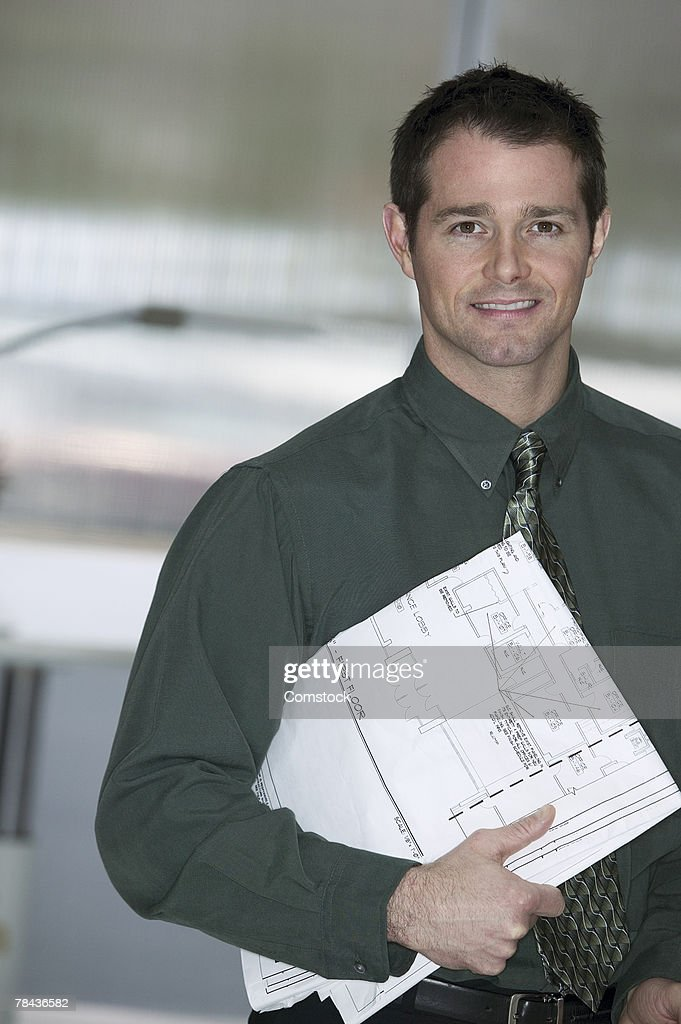 Businessman with architecture plans : Stockfoto