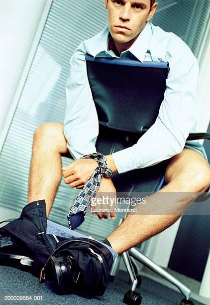 Businessman with arms bound, underwear around ankles, portrait