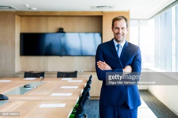 empresário com braços cruzados na sala de diretoria - só um homem - fotografias e filmes do acervo