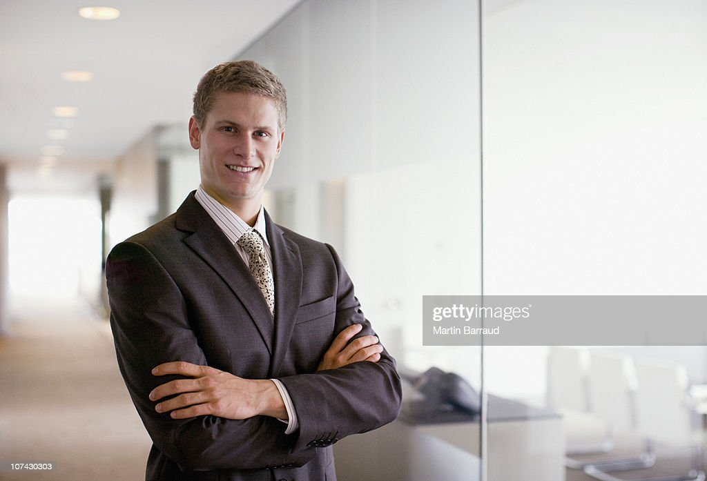 Businessman with arms crossed in office corridor : Stock Photo