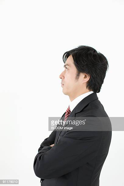 Businessman with arms crossed, side view