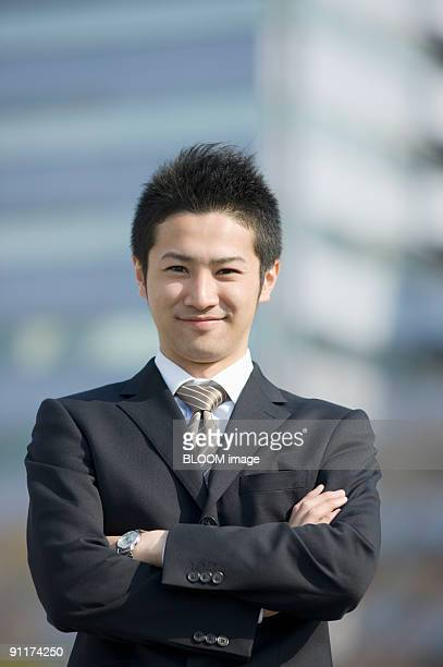 Businessman with arms crossed, smiling