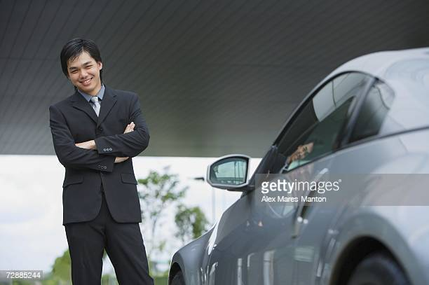 Businessman with arms crossed, standing next to car