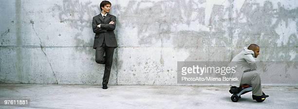 businessman with arms folded leaning against wall watching associate ride child's tricycle - tricycle stock pictures, royalty-free photos & images