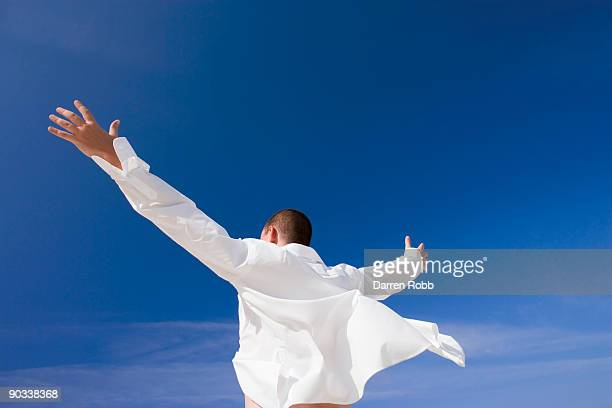 Businessman with arms outstretched towards the sky