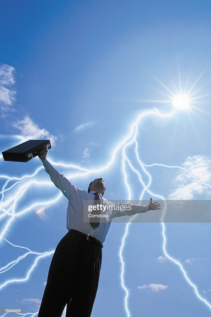Businessman with arms raised and lightning bolts : Stockfoto