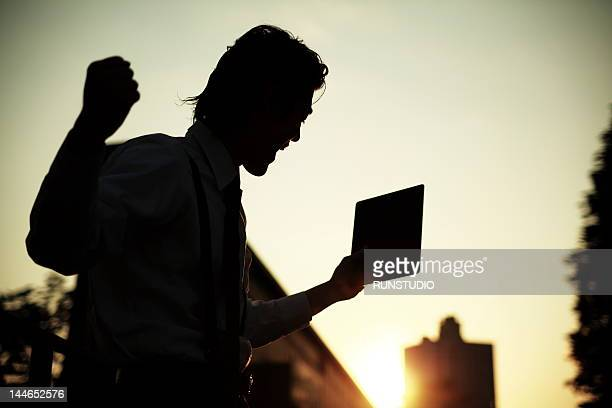 Businessman with arms raised showing success