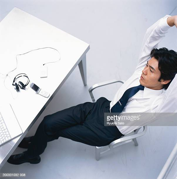 Businessman with arms raised sitting in front of laptop, elevated view