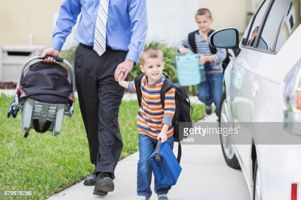 Businessman with baby taking sons to school