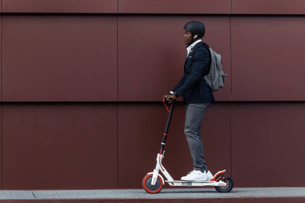 businessman with backpack and cycling helmet on push scooter - scooter stock pictures, royalty-free photos & images