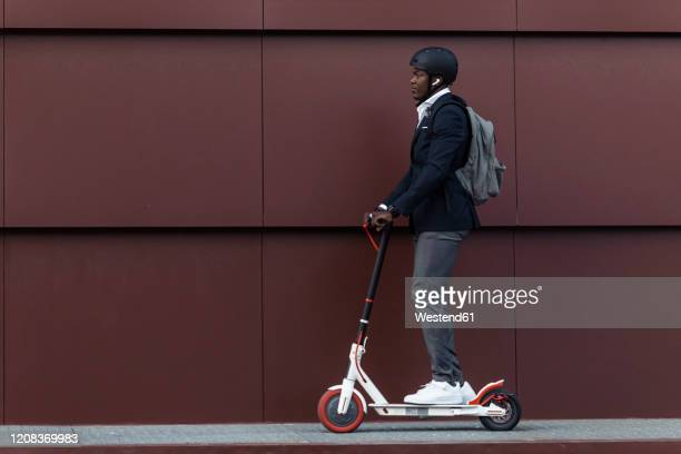 businessman with backpack and cycling helmet on push scooter - electric scooter stock pictures, royalty-free photos & images