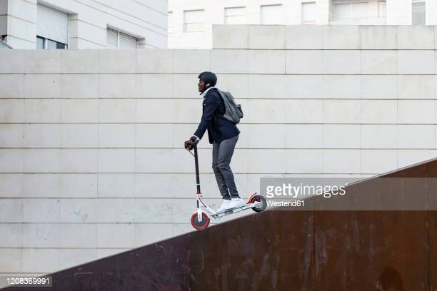 businessman with backpack and cycling helmet on push scooter - helmet stock pictures, royalty-free photos & images