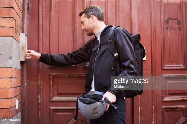 Businessman with backpack entering keycode to close wooden door