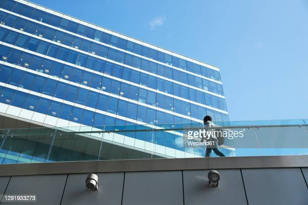 businessman with backpack walking on footbridge by office building in downtown district - low angle view stock pictures, royalty-free photos & images