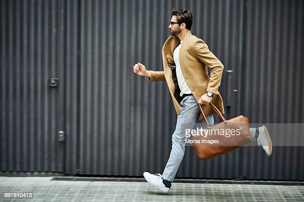 Businessman with bag running on sidewalk in city