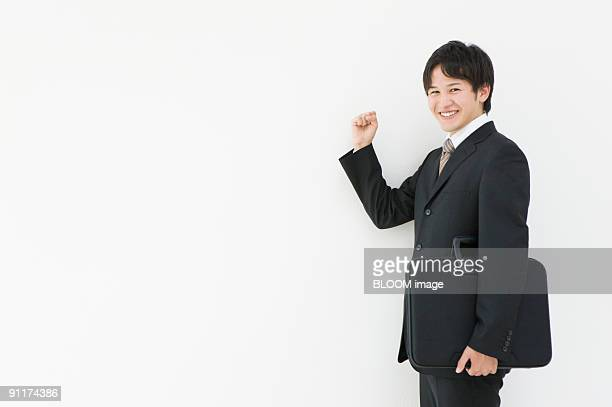 Businessman with bag, smiling, clenching fist