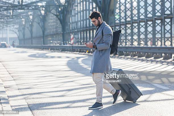 Businessman with baggage crossing the street while looking at cell phone
