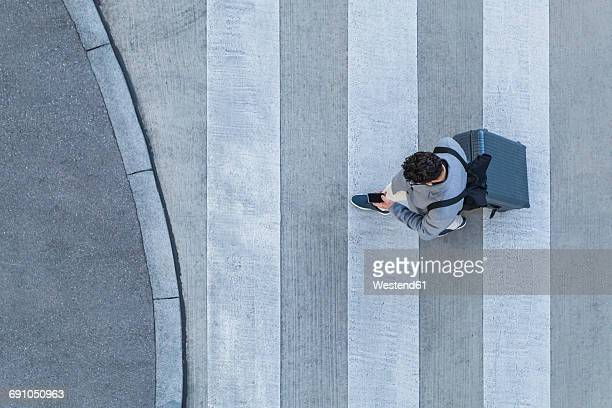 businessman with baggage crossing the street while looking at cell phone, top view - unterwegs stock-fotos und bilder